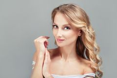 年轻俏丽的妇女肉欲的时尚特写镜头画象白肤金发在灰色背景 免版税库存图片
