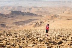 年轻俏丽的妇女背包徒步旅行者上升的石沙漠足迹, Isra 图库摄影