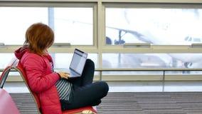 年轻俏丽的妇女自由职业者在有膝上型计算机的机场休息室 影视素材