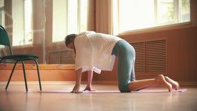 年轻俏丽的妇女行使在瑜伽席子的-屈曲她的后面 股票录像