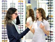 年轻俏丽的妇女试穿在社会媒介的太阳镜和份额使用手机在一家eyewear商店在商店a的帮助下 免版税库存图片