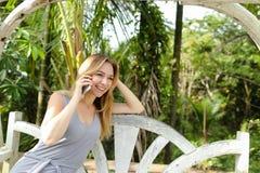 年轻俏丽的妇女谈话由有棕榈的智能手机在背景中,坐摇摆 免版税库存图片
