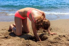 年轻俏丽的少年晒黑了修造在海滩的女孩沙子城堡近由海 库存照片