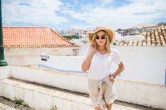 年轻俏丽的摆在街道上的行家快乐的女孩在好日子,有乐趣,时髦的葡萄酒单独衣裳帽子和太阳镜 免版税图库摄影