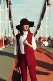 年轻俏丽的模型室外画象在红色服装和黑色的 免版税库存照片