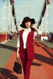 年轻俏丽的模型室外画象在红色服装和黑色的 库存图片
