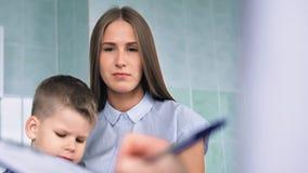 年轻俏丽的母亲和儿子画象咨询的与医生文字食谱 股票录像