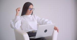 年轻俏丽的白种人女实业家特写镜头画象玻璃工作的在坐在扶手椅子的膝上型计算机与 影视素材