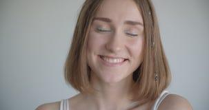 年轻俏丽的白种人女性特写镜头射击有看照相机的头发圆环和闪烁构成的在绝尘室 股票视频