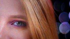 年轻俏丽的白种人女性面孔特写镜头画象与半应用的看照相机与的闪烁桃红色构成的 股票视频