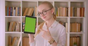 年轻俏丽的白种人白肤金发的女生特写镜头画象玻璃的使用片剂和显示绿色屏幕 股票录像