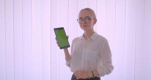 年轻俏丽的白种人白肤金发的女生特写镜头画象玻璃的使用片剂和显示绿色屏幕 影视素材