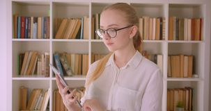 年轻俏丽的白种人白肤金发的女生特写镜头画象玻璃的使用片剂和显示绿色色度 股票录像