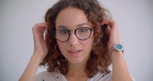 年轻俏丽的长发卷曲白种人特写镜头画象女性在微笑的玻璃诱人地看照相机 股票视频