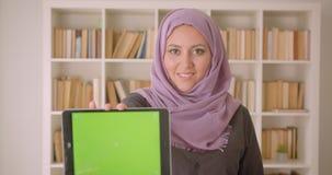 年轻俏丽的阿拉伯人特写镜头画象女性在hijab使用片剂和显示绿色色度屏幕对照相机  股票视频