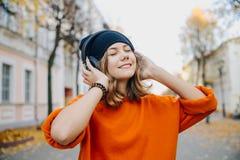 年轻俏丽的黑帽会议听的音乐的行家青少年的女孩通过在秋天街道上的耳机 库存照片
