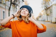 年轻俏丽的黑帽会议听的音乐的行家青少年的女孩通过在秋天街道上的耳机 免版税库存图片