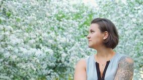 年轻俏丽的tattoed女孩在苹果树开花的开花享用 股票视频