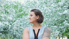 年轻俏丽的tattoed女孩在苹果树开花的开花享用 影视素材
