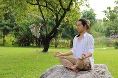 年轻信奉瑜伽者人画象做瑜伽凝思的白色衬衣的,当坐在岩石的莲花坐在美好的室外p时 库存照片