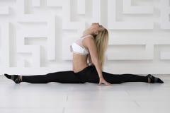 年轻信奉瑜伽者女子实践的瑜伽概念,舒展,分裂, Hanumanasana姿势,全长,白色演播室背景 库存照片