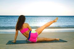 年轻做核心锻炼的海滩的健身亚裔妇女 图库摄影