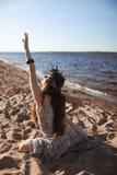 年轻健康在海滩的女子实践的瑜伽在日出 免版税库存照片