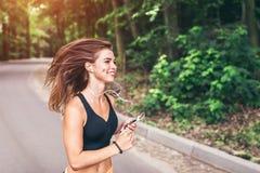 年轻健身女孩跑的和听的音乐在公园 免版税库存图片