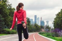 年轻健身妇女赛跑者在跑前舒展她的腿户外 库存图片