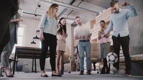 年轻偶然同事使用与球在现代办公室 愉快的不同种族的雇员享受体育活动慢动作 股票视频