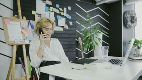 年轻偶然妇女在书桌使用膝上型计算机,回答的电话,谈话坐电话 股票录像