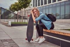 年轻偶然clothessitting的行家白肤金发的女孩在反对摩天大楼的一条长凳,休息在乘坐在滑板以后 库存图片