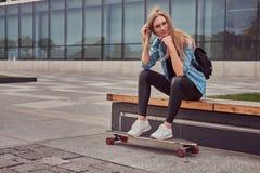 年轻偶然clothessitting的行家白肤金发的女孩在反对摩天大楼的一条长凳,休息在乘坐在滑板以后 免版税图库摄影