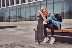 年轻偶然clothessitting的行家白肤金发的女孩在反对摩天大楼的一条长凳,休息在乘坐在滑板以后 免版税库存图片