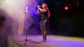 年轻充分的成长的红头发人女歌手在话筒的阶段在一阵烟幕 股票视频