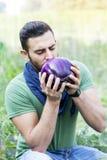 年轻农夫在他的庭院里嗅到紫色茄子 免版税库存照片