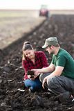 年轻农夫检查土,当拖拉机犁领域时 免版税库存图片