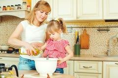 年轻准备面团的母亲和逗人喜爱的矮小的女儿,在厨房里烘烤曲奇饼和有乐趣 免版税图库摄影