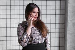 年轻办公室妇女的关闭谈话与某人她的手机的,当调查与愉快的脸面护理时的距离 免版税库存照片