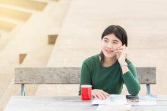 年轻办公室妇女谈话与某人她的有H的手机的 库存照片