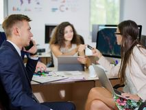 年轻办公室工作者在他们的一个新的项目的办公室工作 免版税库存图片