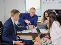 年轻办公室工作者在他们的一个新的项目的办公室工作 免版税库存照片