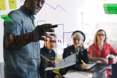 年轻办公室工作者在桌上,当显示想法的非洲男性同事坐玻璃墙在见面期间,小组时 库存图片