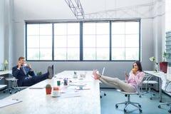 年轻办公室工作者,午休事务在桌上把他们的脚放 免版税库存图片