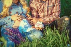 年轻加上一起看礼物儿童衣裳和婴儿鞋子-愉快的人民的孕妇准备好家庭lif 免版税库存照片