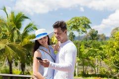年轻加上在使用智能手机拥抱的热带森林视图快乐的男人和妇女的细胞巧妙的电话 免版税库存图片