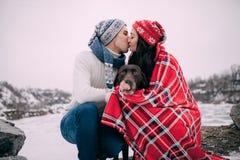 年轻加上在红色格子花呢披肩包裹的狗是坐和亲吻在冬天步行期间 库存图片