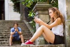 年轻加上智能手机坐台阶在镇里 免版税库存照片