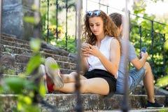 年轻加上智能手机坐台阶在镇里 库存图片
