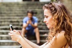 年轻加上智能手机坐台阶在镇里 免版税库存图片